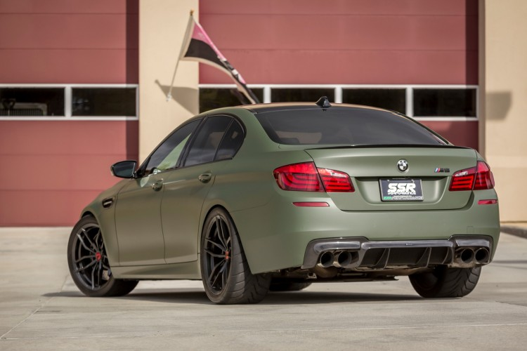 A Military Green BMW M5 With Vorsteiner Wheels And Aero Installed